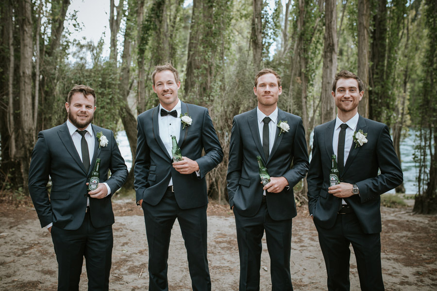 The groomsment looking handsome and enjoying a cold one from Kelsey and Matt's Wanaka wedding captured by Wanaka wedding photographers Alpine Image Company.
