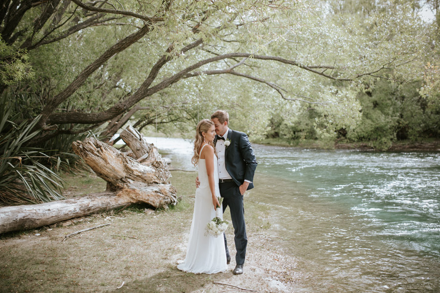 The happy Bride and Groom on their wedding day by the Clutha River in Wanaka, New Zealand. Wanaka wedding photography by Alpine Image Company.