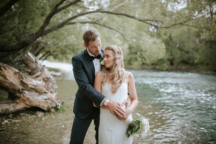 Kelsey and Matt looking gorgeous by the Clutha River in Wanaka on their wedding day. Wanaka wedding photography by Alpine Image Company.
