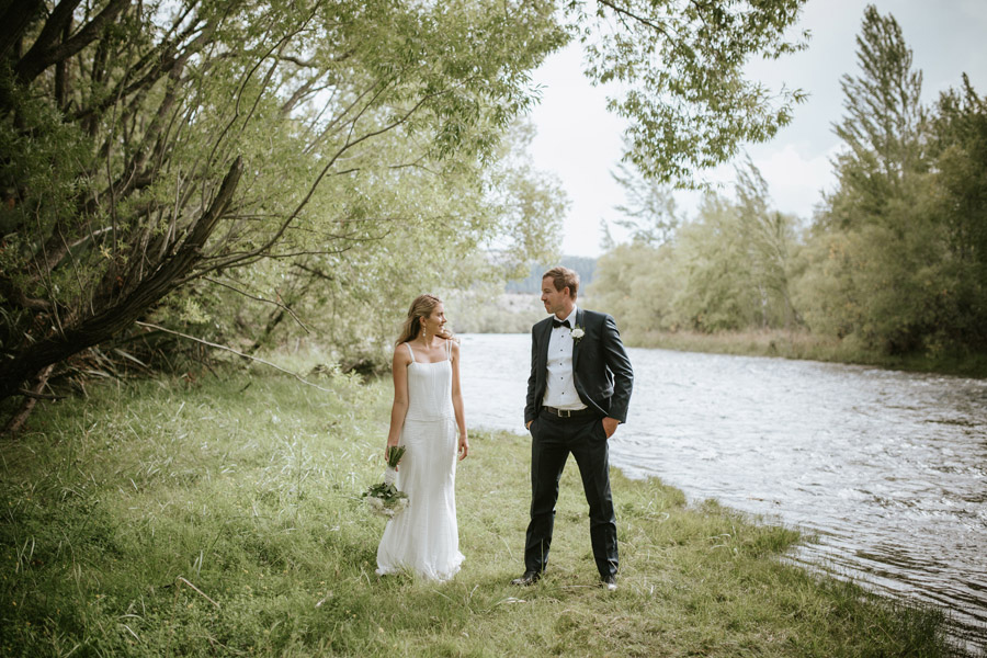 Kelsey and Matt by the Clutha River on their wedding day in Wanaka, New Zealand. Wanaka wedding photogaphy by Alpine Image Company.
