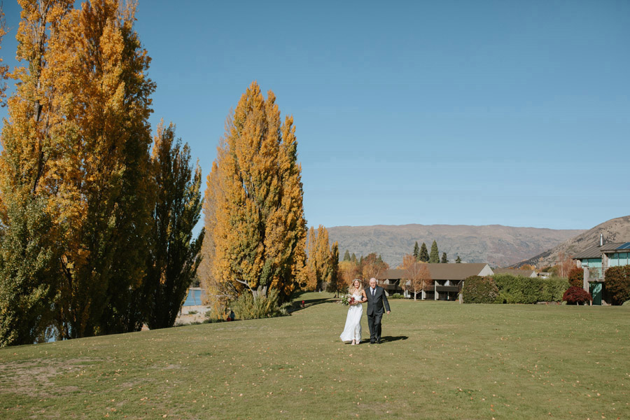 The bride walking down for her Wanaka wedding at Edgewater Resort, captured by Wanaka wedding photographers Alpine Image Company.