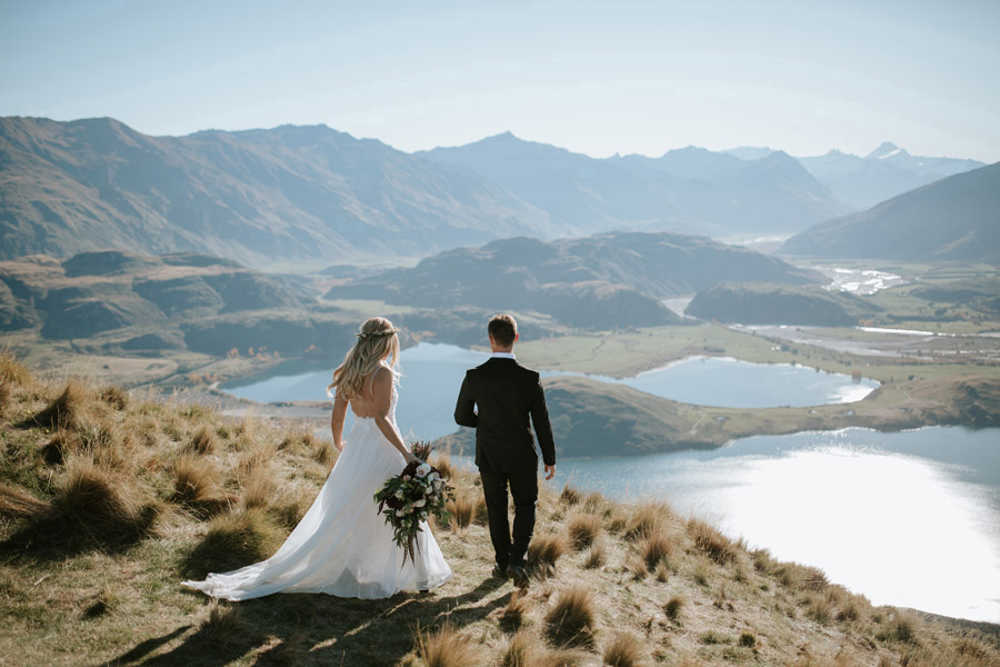 Estelle and Stas looking out over Lake Wanaka on their autumn wedding day. Photography by Alpine Image Company.