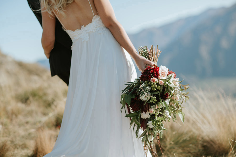A gorgeous detail shot of Estelle's wedding flowers and wedding dress by Wanaka wedding photographers, Alpine Image Company.