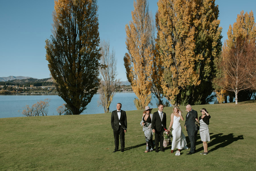 Excited guests waiting for the Bride and Groom's arrival by helicopter on this Wanaka wedding day. Photography by Alpine Image Company.