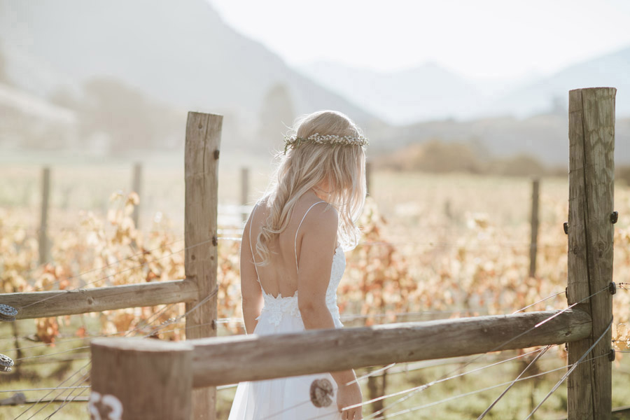 A stunning bride walking through the vines on her Wanaka wedding day. Photography by Alpine Image Company.