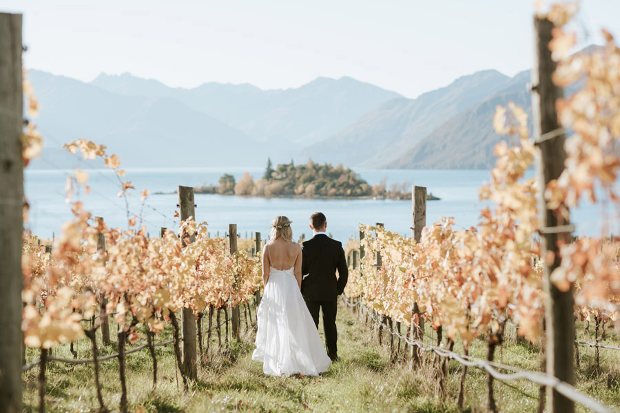 The bride and groom looking out at Ruby Island, Wanaka on their Wanaka wedding day photographed by Alpine Image Company.
