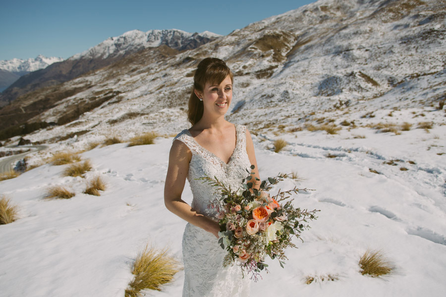 The beautiful bride Katie, looking gorgeous with the spring snow in the background on her Queenstown wedding day. Wedding photo by Queenstown wedding photographer Alpine Image Company.