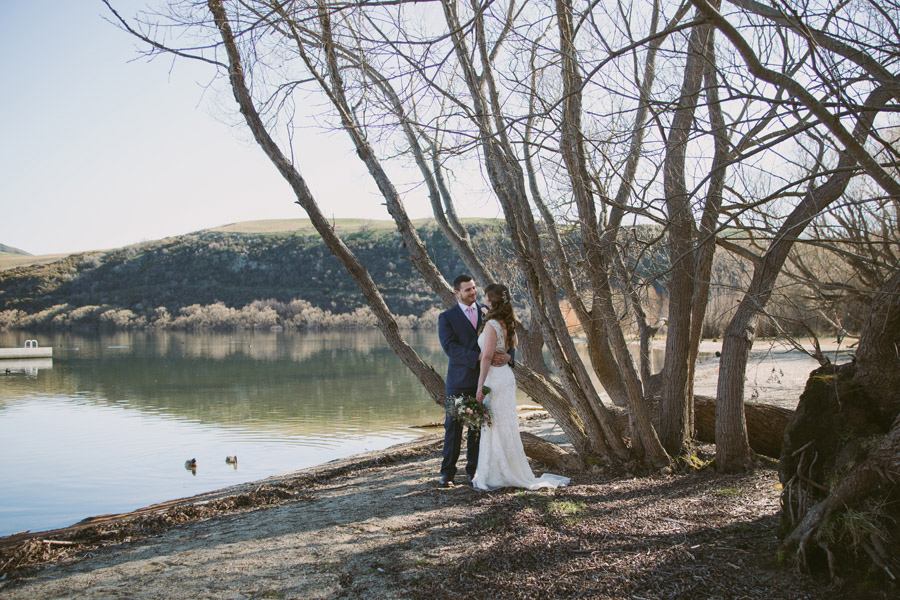 Katie & Bernard looking gorgeous on their Queenstown wedding day having some of their wedding photos down by Lake Hayes.