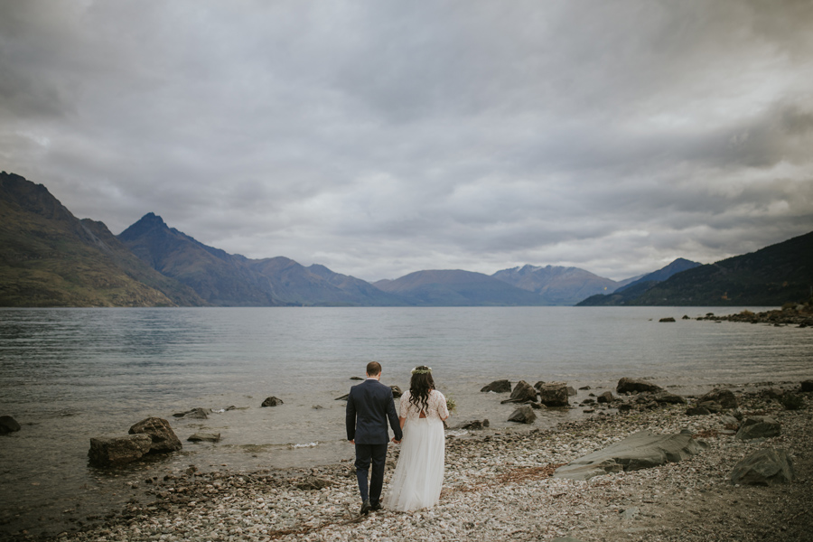 A bride and groom walk towards a lake. There are mountains in the distance and cloudy, stormy skies.