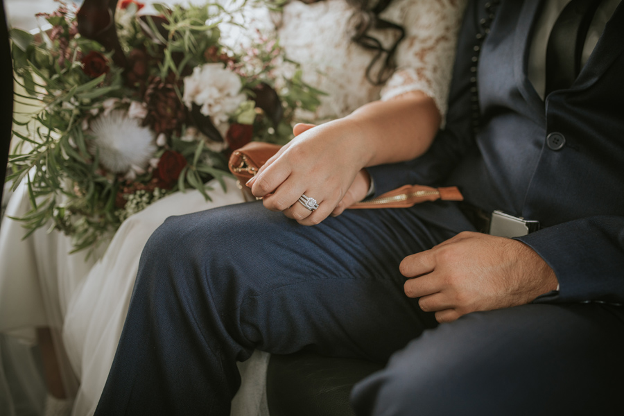 A bride and groom hold hands, showing off the bride's beautiful engagement ring.