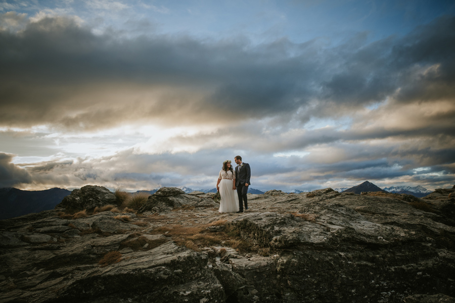 A bride and groom walk towards the camera. They are walking along a rocky mountain with blue, stormy skies behind them.