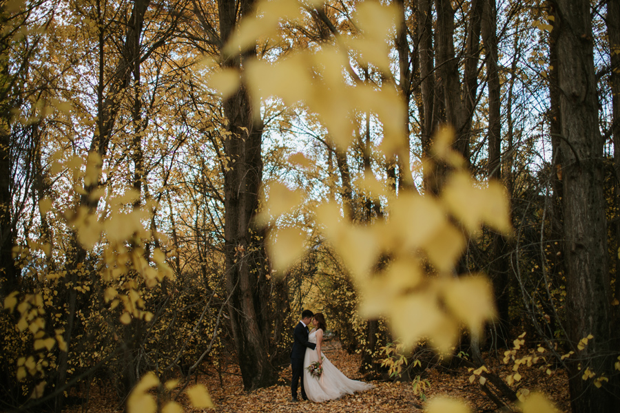 Jamie and Eric enjoying a moment of calm in the autumn leaves on their wanaka wedding day.