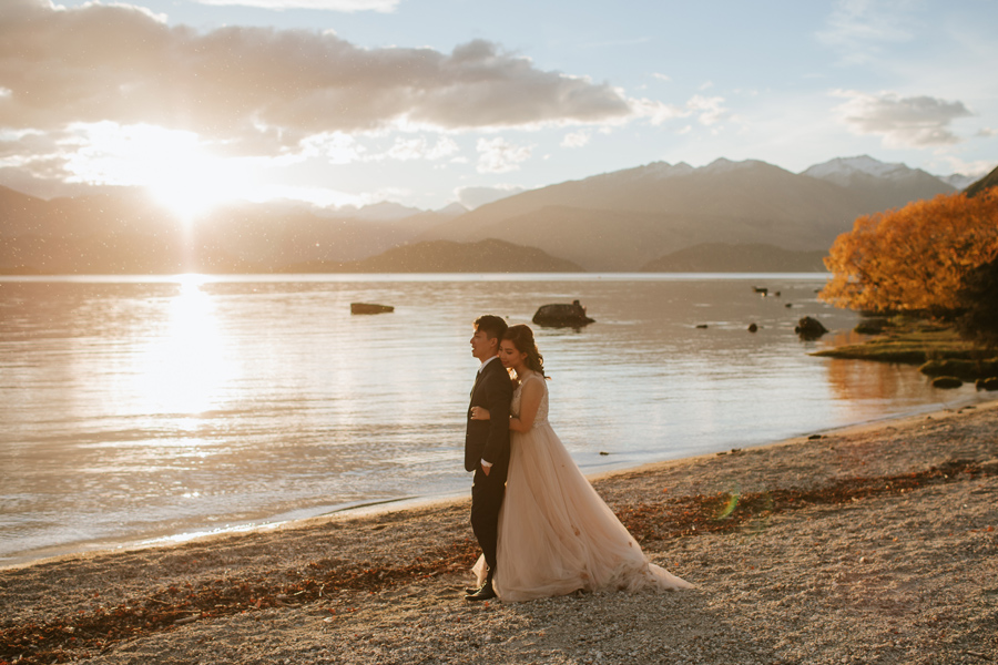 Jamie and Eric cuddling by the lake in the last of the golden hour. We love this time of year for an autumn wanaka wedding.
