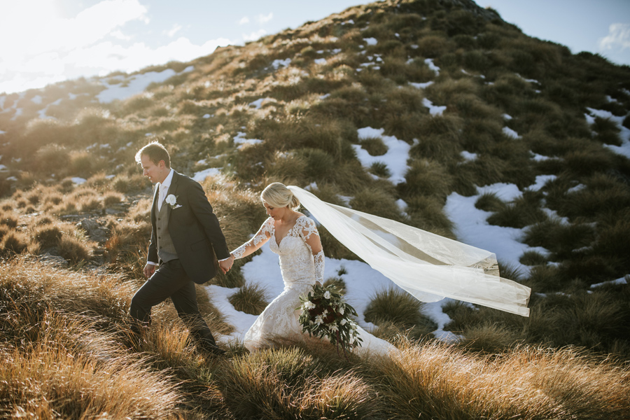 A bride and groom walk, holding hands, across a mountain top on their wedding day.