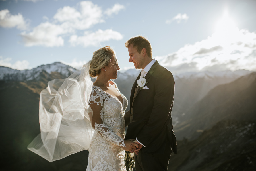 A bride and groom look at each other smiling. They are standing on a mountain top on their wedding day.