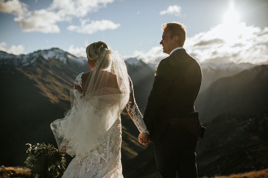A close up photo of a bride and groom on their wanaka wedding day. They are standing on a mountain top as the sun is setting