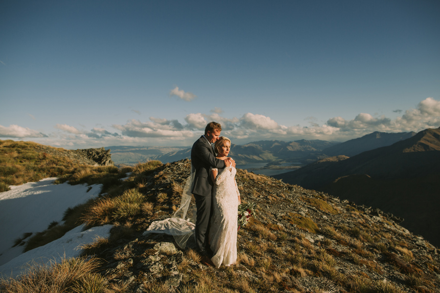 A bride and groom stand on a mountain top, with a lake in the distance on their Wanaka wedding day. With photography by Alpine Image Company