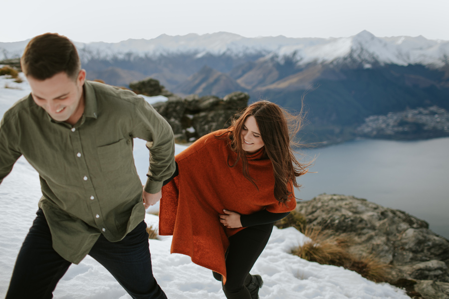 A couple walk together laughing in the snow on their engagement shoot. The Queenstown mountains that surround them are snow capped and beautiful. With photography by Alpine Image Company