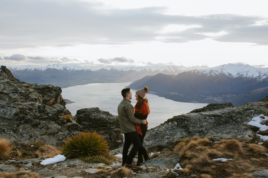 A couple share a warm embrace on their Queenstown engagement shoot. They are high in the mountains, with Lake Wakitipu behind them and snow capped mountains in the distance. With photography by Alpine Image Company