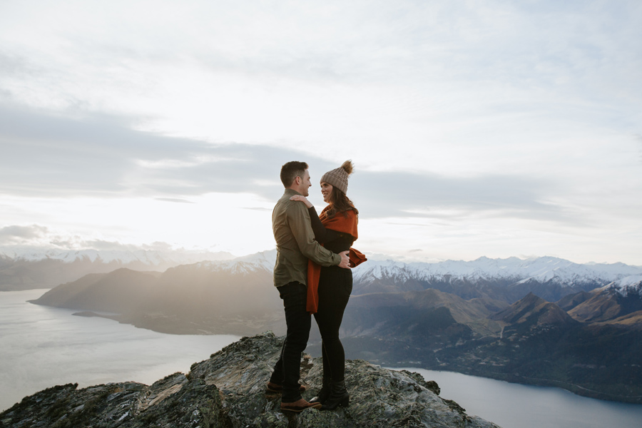 A couple stand on Cecil Peak in an embrace, on their Queenstown Wedding shoot. The mountains in the distance are covered in snow, and the lake sits below them. With photography by Alpine Image Company