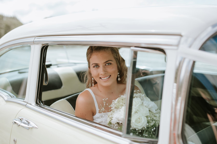The gorgeous bride arriving in classic car to her Luggate/Wanaka wedding captured by Wanaka wedding photographers Alpine Image Company.