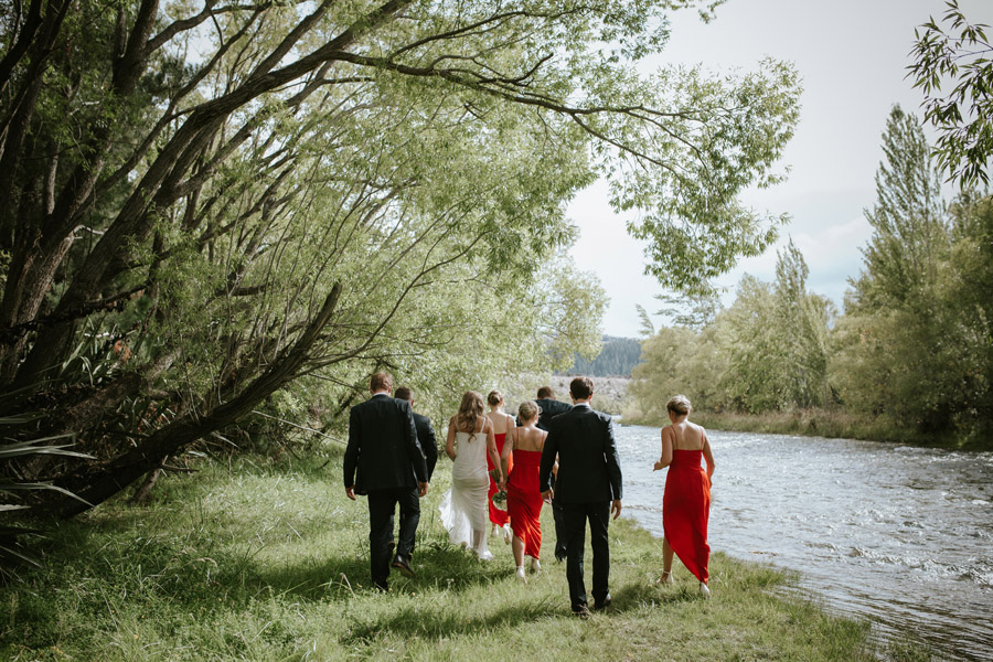Kelsey, Matt and their bridal party enjoying the sun by the river on their Wanaka wedding day. Wanaka wedding photography by Alpine Image Company.