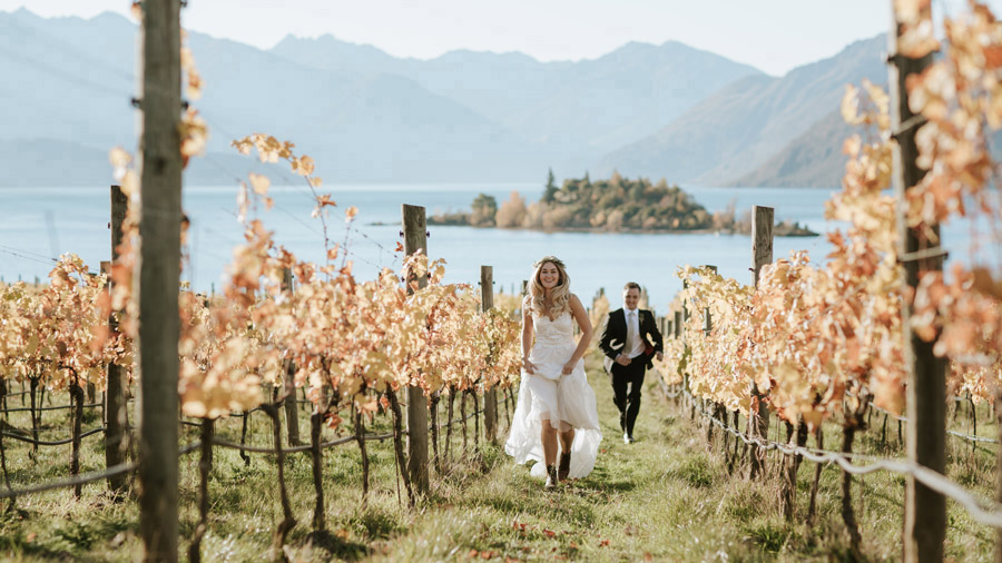 Running through the vines on their Wanaka wedding day at The Rippon Hall. Photographed by Wanaka wedding photographers Alpine Image Company.
