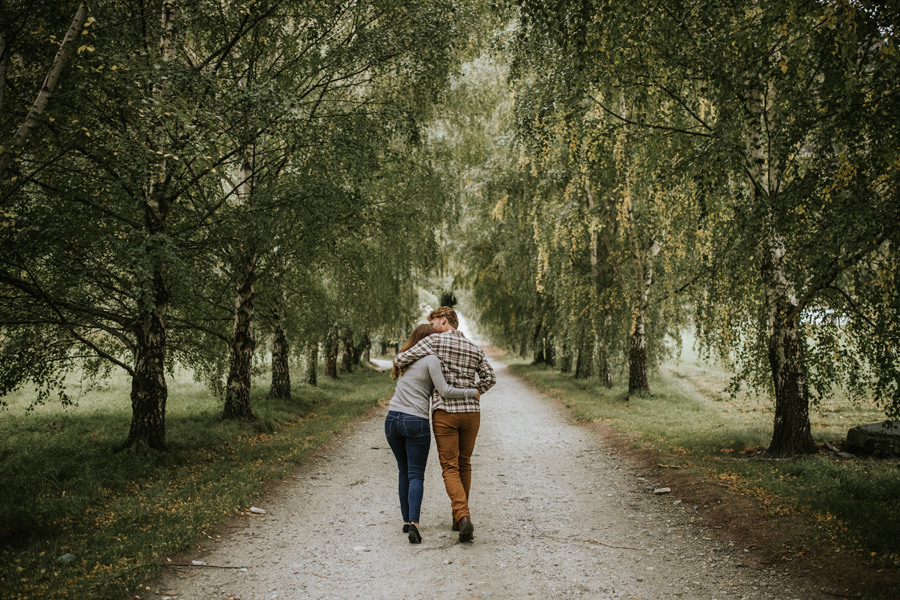 Lesley and Cameron head down a tree lined driveway on their Queenstown Engagement Shoot.