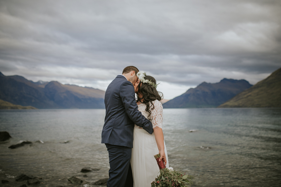 A bride and groom share a kiss in front of a lake. The skies are stormy and there are mountains in the background.