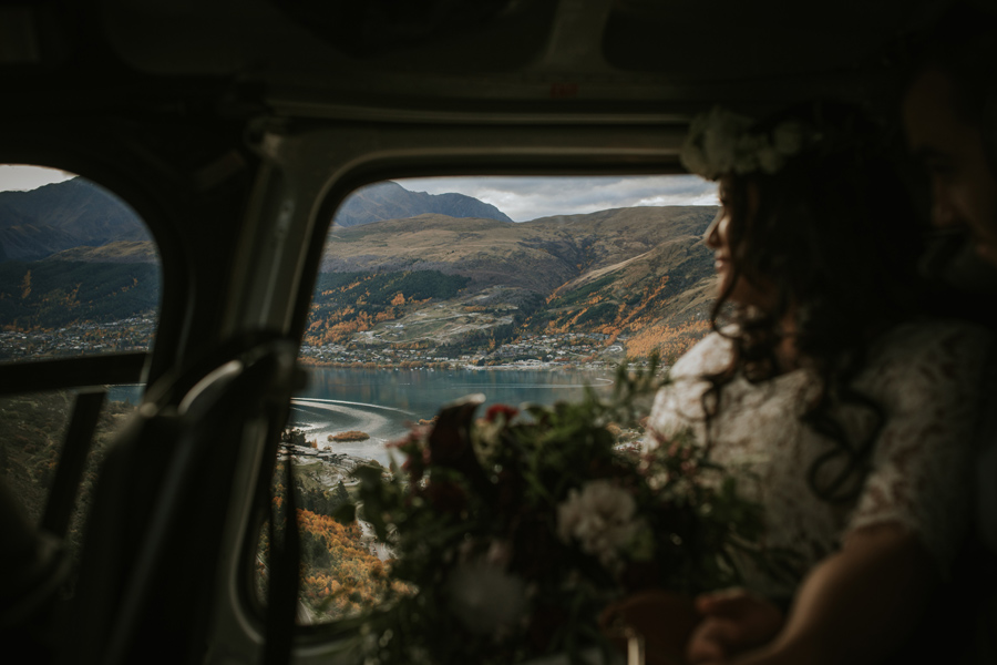A bride sits in a helicopter and it hovers over a lake and mountains.