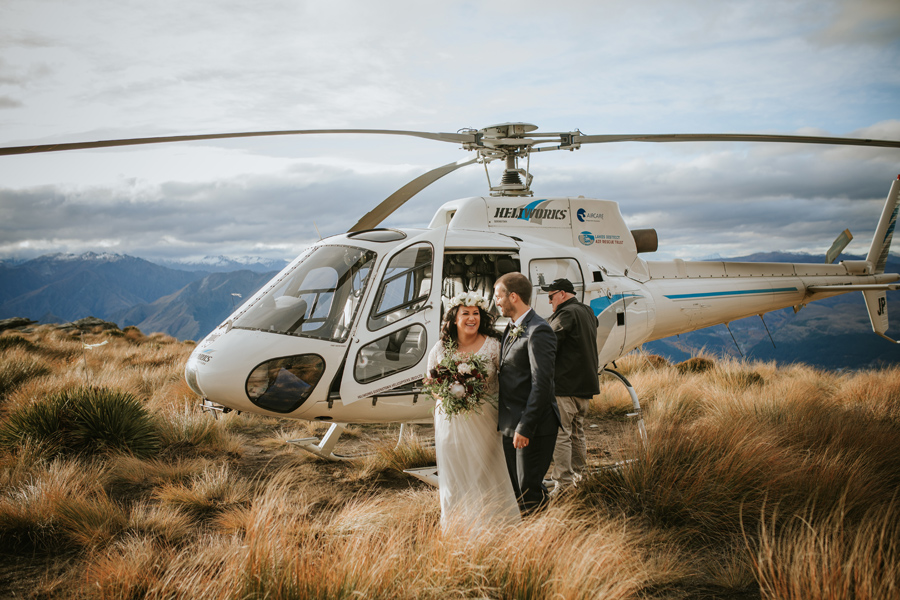 A bride and groom exit a helicopter on top of a mountain.