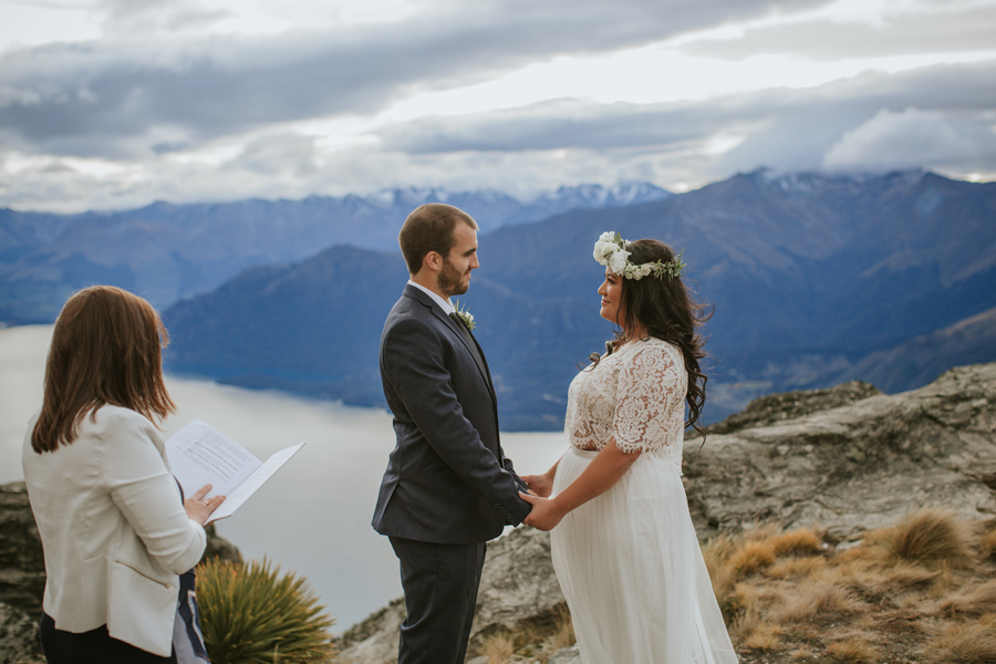 A bride and groom face each other during their mountain top wedding ceremony.