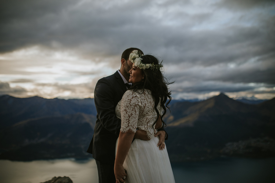 A bride and groom embrace on top of a mountain. The light hits the brides face as she smiles. Lakes and mountains are visible behind them in the distance.