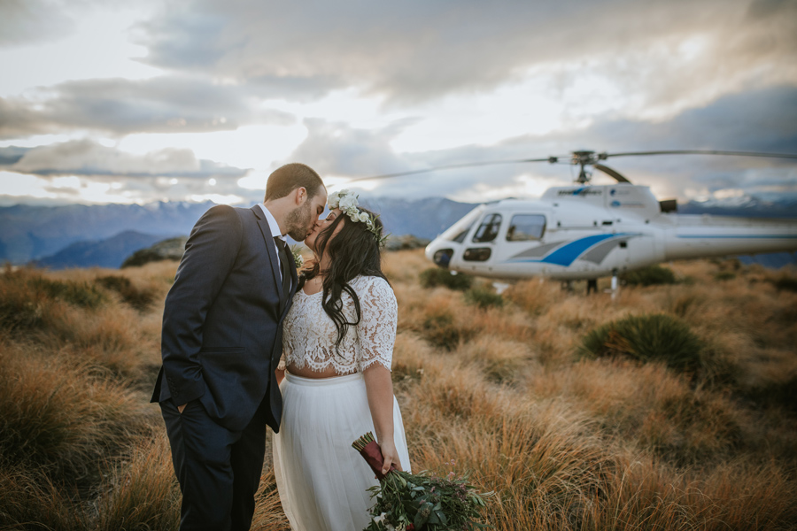 A couple share a kiss in front of a helicopter on their wedding day.