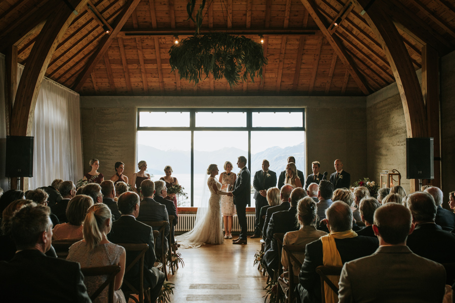 Anna and Nick hold hands at the end of the aisle as their guests watch on. With photography by Alpine Image Company