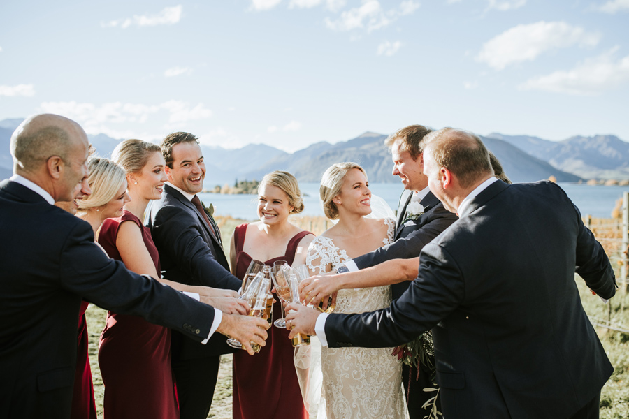 A bride and groom and their bridal party cheers with their wedding drinks. With photography by Alpine Image Company