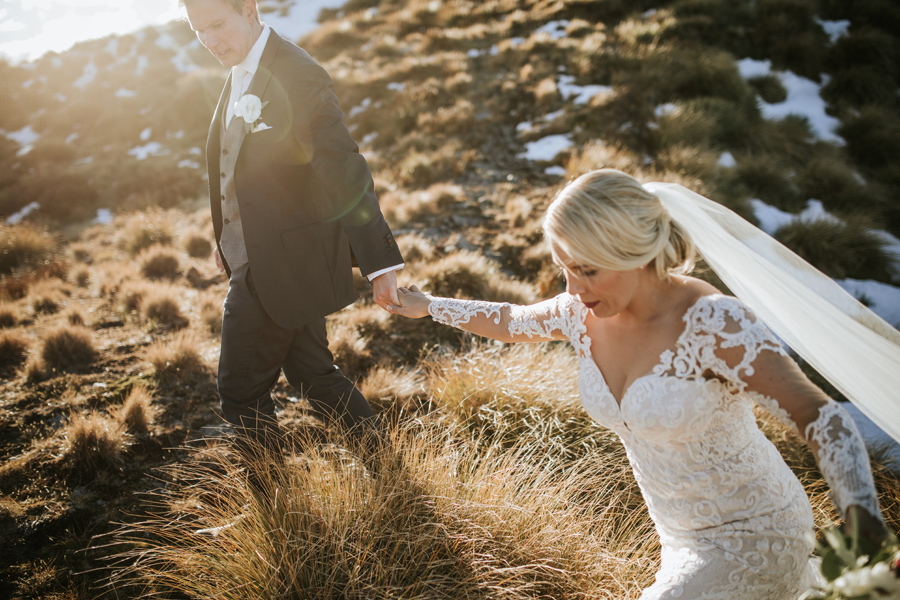 A bride and groom hold hands as they walk on mountain grasses on their wedding day. With photography by Alpine Image Company