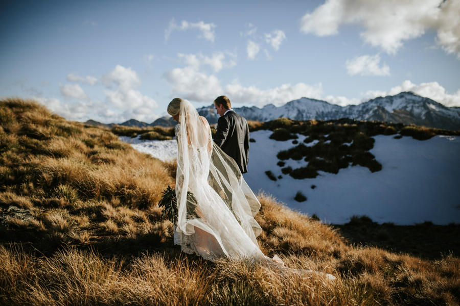 A bride and groom walk away from the camera, with a snowcapped mountain in the background, on their wedding day. With photography by Alpine Image Company