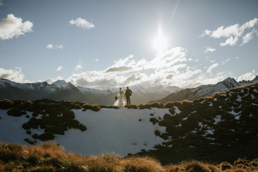 A bride and groom stand in the distance, on a mountain top, as the sun sets behind them. There is snow on the ground and mountains in the distance. With photography by Alpine Image Company