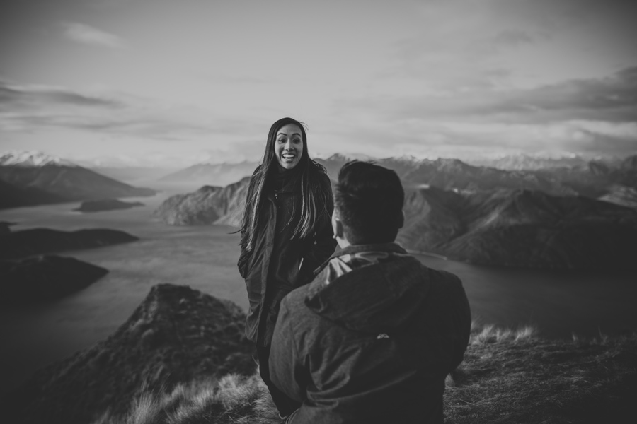 Justin gets down on one knee as his fiance turns around with a huge smile on her face. They are on top of a mountain and the lake and scenery behind them is spectacular.