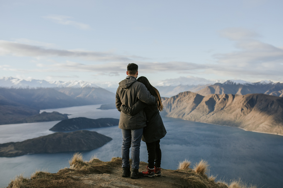 A newly engaged couple embrace as they look out onto Lake Wanaka from a mountain top peak. There are snow capped mountains surrounding them.