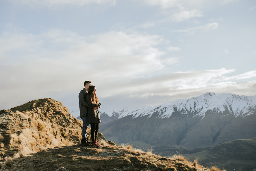 A couple embrace on a mountain side as they look out onto the setting sun. There are snow capped mountains in the background and they are happy together.