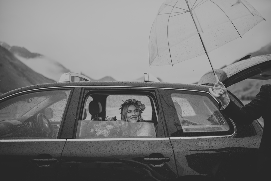 A gorgeous bride looks out of her wedding car. It is raining but she is happy, and there is an umbrella ready and waiting for when she exits the car. With photography by Alpine Image Company