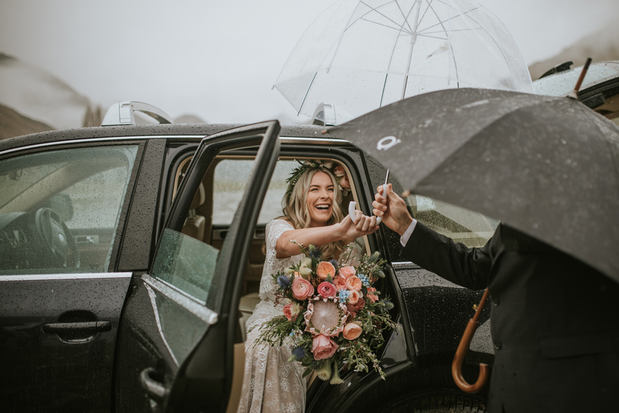 A bride exits her wedding car laughing. It is raining and she holds an umbrella to keep from getting wet. With photography by Alpine Image Company
