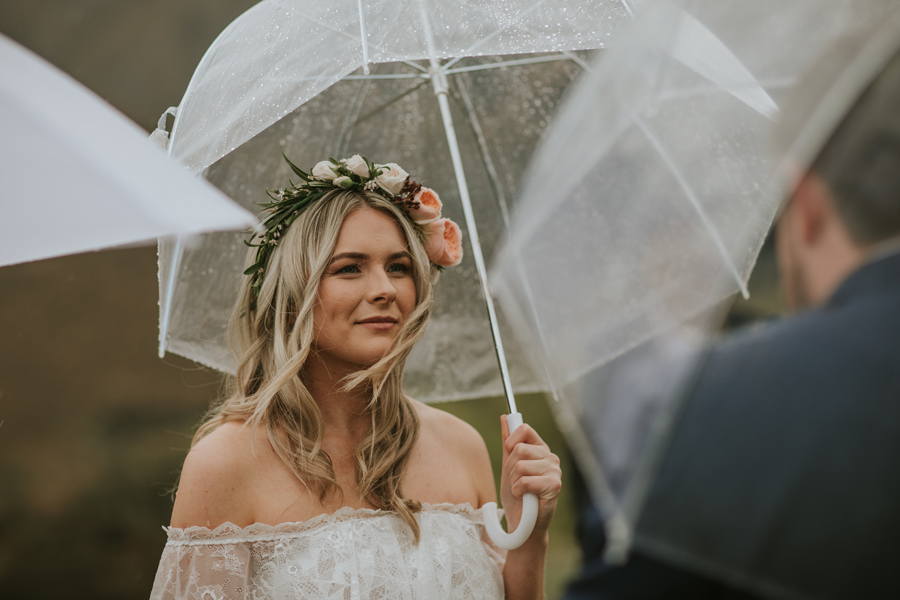 A gorgeous bride and groom exchange their vows on the Queenstown Wedding Day. They are standing in the rain and umbrellas cover them. With photography by Alpine Image Company