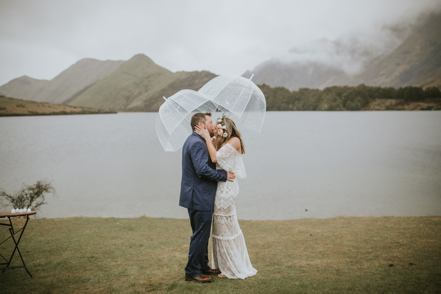 A bride and groom share their wedding kiss in the rain on their Queenstown wedding day. With photography by Alpine Image Company