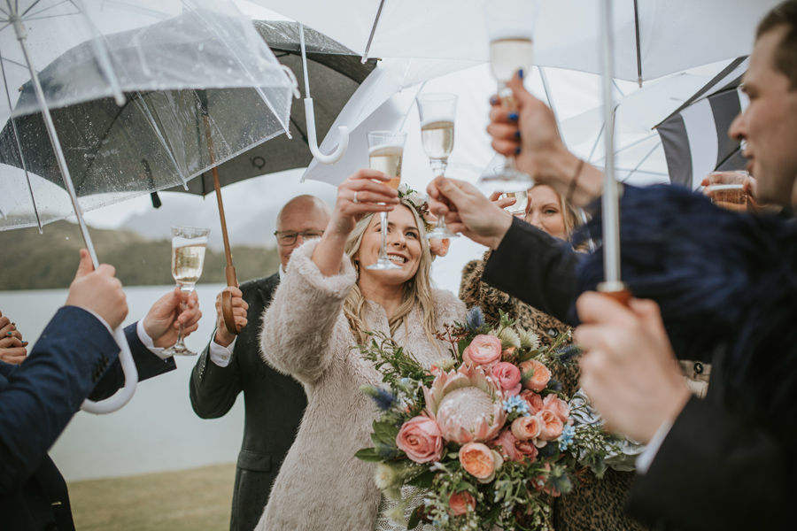 A group of happy wedding guests share a cheers. They all stand under umbrellas because it is raining. The bride looks happy! With photography by Alpine Image Company