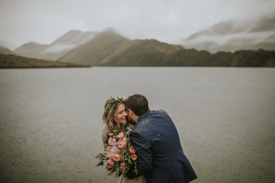 A bride and groom laugh and cuddle together in the rain on their wedding day. They are at Moke Lake for their Queenstown wedding. There are mountains in the background. With photography by Alpine Image Company
