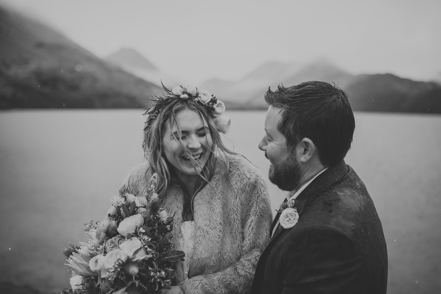 Mikaela and Tom laugh together in the rain on their wedding day at Moke Lake in Queenstown. There are misty mountains behind them, and they stand in front of Moke Lake. With photography by Alpine Image Company