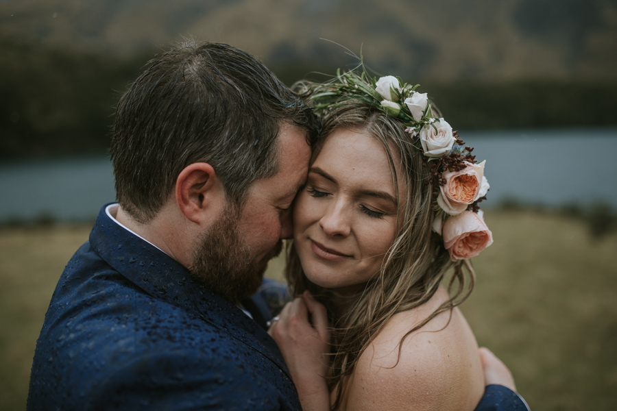 A bride and groom share a warm embrace as they stand in the rain on their Queenstown Wedding at Moke Lake. With photography by Alpine Image Company